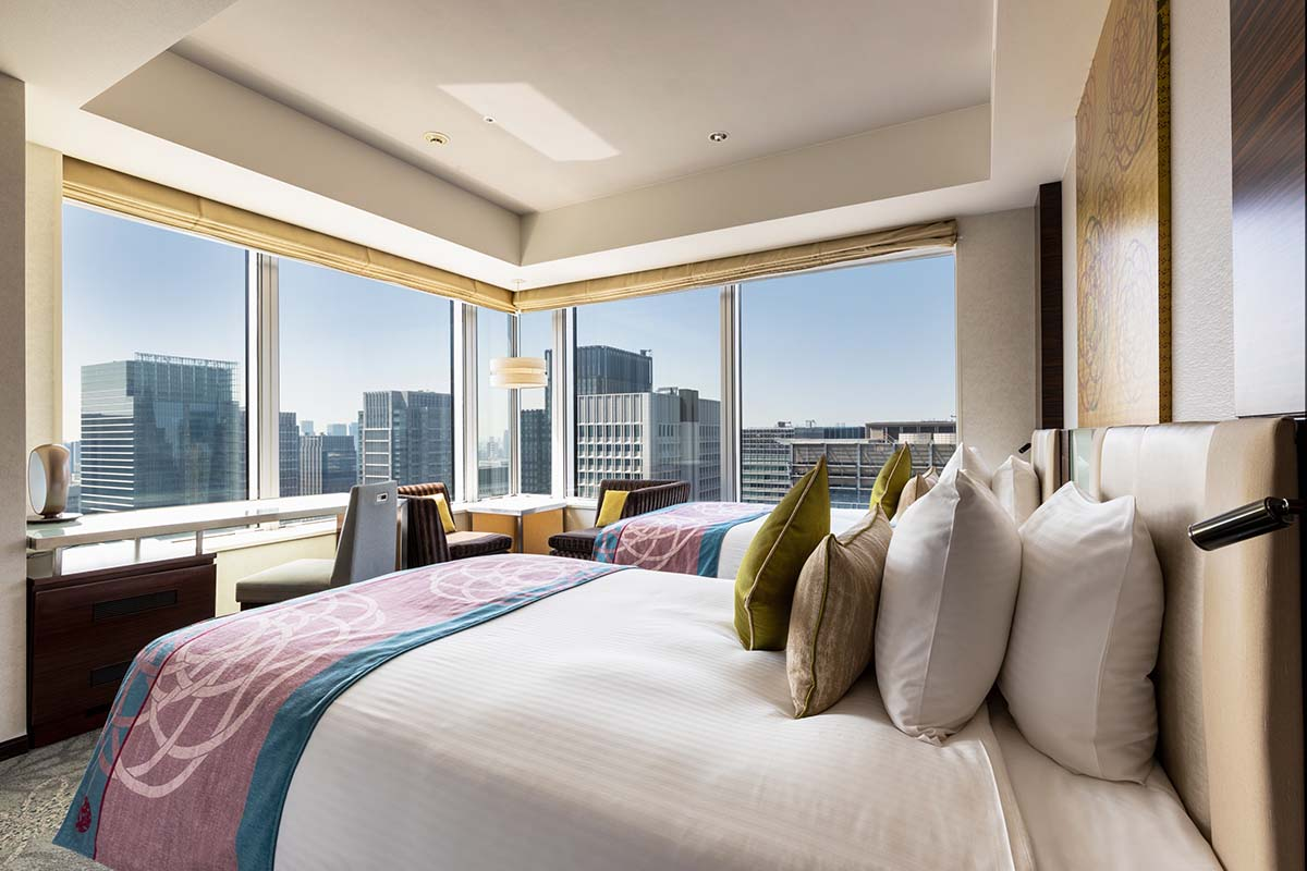 4 star hotel in Tokyo, Japan guest room interior taken from inside a room with 2 beds, 2 sofa, desk, and chair overlooking city view through window